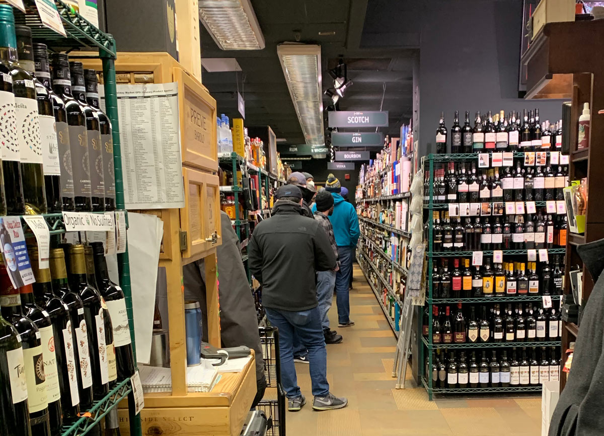 Men stand in line at a grocery store's liquor aisle for an allocated whiskey drop.