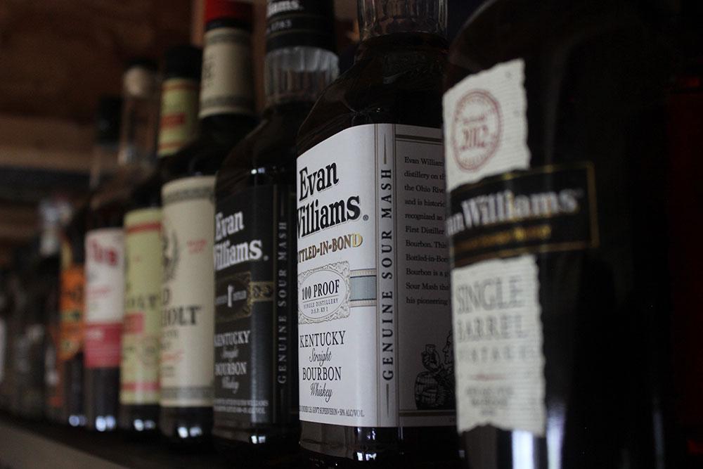 Bourbon bottles sitting on a shelf.